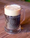 在一张木桌上的杯子黑啤酒 免版税库存图片