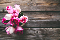 在一张木桌上的桃红色玫瑰 葡萄酒 花 免版税库存照片