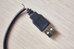 在一张木桌上的残破的usb缆绳 免版税库存照片