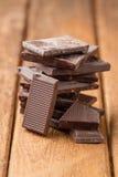 在一张木桌上的残破的黑暗的巧克力块 免版税库存照片