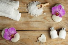 在一张木桌上的温泉集合与心脏由按摩的石头制成、腌制槽用食盐、毛巾和桃红色兰花花和身体 库存照片