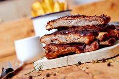 在一张木桌上的烤肉肋骨 免版税库存图片