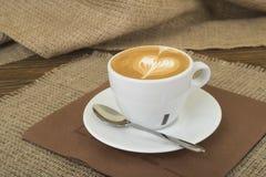 在一张木桌上的热的拿铁艺术咖啡杯c茶碟 图库摄影