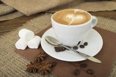 在一张木桌上的热的拿铁艺术咖啡杯c茶碟 免版税库存图片