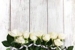 在一张木桌上的白玫瑰 库存照片