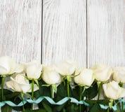 在一张木桌上的白玫瑰 免版税库存图片
