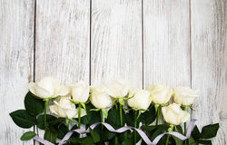 在一张木桌上的白玫瑰 免版税库存照片