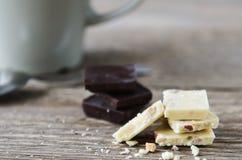 在一张木桌上的白色和黑暗的巧克力 图库摄影