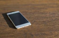 在一张木桌上的白色电话 免版税库存照片