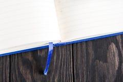 在一张木桌上的白色笔记本 在笔记薄谎言全部附近被弄皱的纸 免版税库存照片
