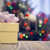 在一张木桌上的礼物盒反对装饰的圣诞树 库存照片