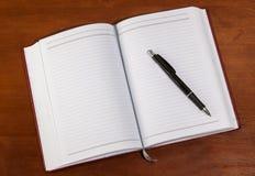 在一张木桌上的笔记本 图库摄影