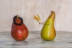 在一张木桌上的红色和黄色梨 两个恋人梨 梨的构成 免版税库存照片