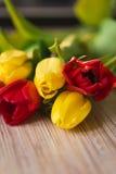 在一张木桌上的红色和黄色郁金香 库存图片