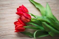 在一张木桌上的红色郁金香 图库摄影