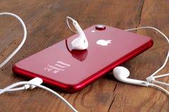 在一张木桌上的红色iPhone XR与白色耳机 免版税库存图片