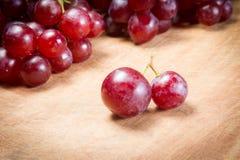 在一张木桌上的红葡萄 免版税图库摄影