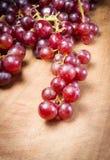 在一张木桌上的红葡萄 免版税库存照片