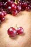 在一张木桌上的红葡萄 库存照片