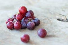 在一张木桌上的红葡萄 免版税库存图片