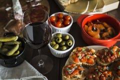 在一张木桌上的红酒和塔帕纤维布盘 免版税库存照片