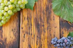 在一张木桌上的绿色和蓝色葡萄 免版税库存照片