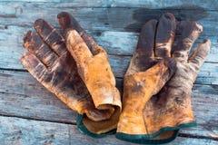 在一张木桌上的老卑鄙的勾当手套弄脏与油膏和油 高危险和辛苦行业的表示法 免版税库存图片