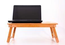 在一张木桌上的膝上型计算机 库存图片