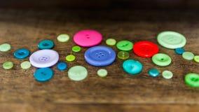 在一张木桌上的色的按钮 免版税库存照片