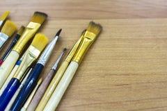 在一张木桌上的艺术性的刷子 背景 库存照片