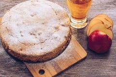 在一张木桌上的苹果饼 苹果饼、汁液和红色苹果计算机 免版税图库摄影