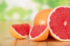 在一张木桌上的葡萄柚段 免版税库存图片