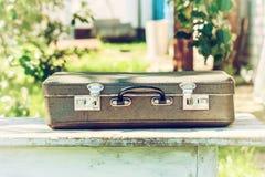 在一张木桌上的葡萄酒棕色皮革手提箱 旅行的概念 自然光 免版税图库摄影