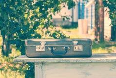 在一张木桌上的葡萄酒棕色皮革手提箱 旅行的概念 自然光 库存图片