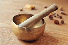 在一张木桌上的西藏唱歌碗 免版税库存图片