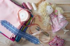 在一张木桌上的逗人喜爱的手工制造玩偶与五颜六色的织品、被编织的鞋带、淡色丝带和缝合的家具 库存照片