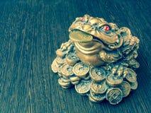 在一张木桌上的金钱青蛙与在它的嘴的一枚硬币 库存图片