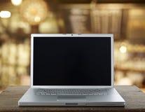 在一张木桌上的铝膝上型计算机 免版税库存照片