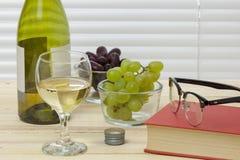 在一张木桌上的阅读书与一杯白葡萄酒 免版税图库摄影