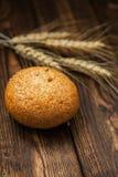 在一张木桌上的面包和麦子耳朵 免版税图库摄影