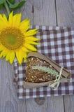 在一张木桌上的面包在向日葵旁边说谎 免版税库存照片