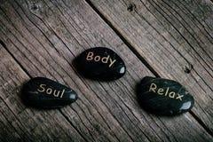 在一张木桌上的黑石治疗 黑色概念花温泉向毛巾健康扔石头 库存图片