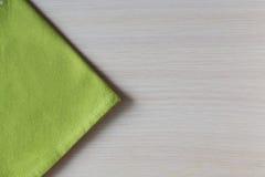 在一张木桌上的绿色餐巾 免版税库存照片