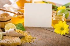 在一张木桌上的养蜂业产品与您的文本的卡片 免版税库存照片