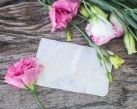 在一张木桌上的Lisianthus花束与空白的笔记 库存图片