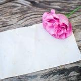 在一张木桌上的Lisianthus花束与空白的笔记 免版税库存图片