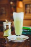 在一张木桌上的Matcha拿铁在咖啡馆 免版税库存照片