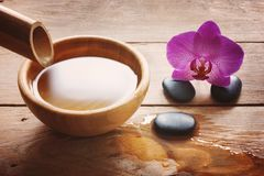 在一张木桌与一个竹词根和一个碗上的温泉做法的构成水,石头和一朵明亮的兰花开花 免版税图库摄影