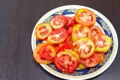 在一张木桌安置的板材的蕃茄切片 在的焦点 免版税图库摄影