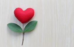 在一张木桌安置的红色心脏连接用t分支  免版税库存照片